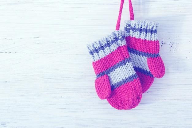 Piccoli bambini dei guanti del bambino che appendono sopra il fondo bianco di legno rustico. Foto Premium
