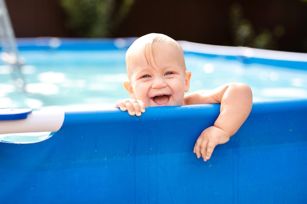 Il piccolo bambino si diverte con un tuffo in piscina.