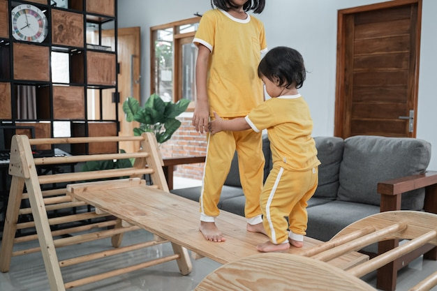 Il piccolo bambino tiene i piedi delle sue sorelle mentre gioca nei giocattoli del triangolo pikler
