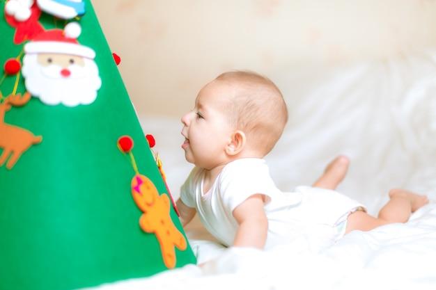 Piccolo neonato gioca con l'albero di natale sdraiato sorprendentemente guarda sotto il giocattolo degli studi sull'albero di natale