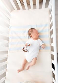 Piccolo bambino sdraiato nella culla bianca al giorno di sole