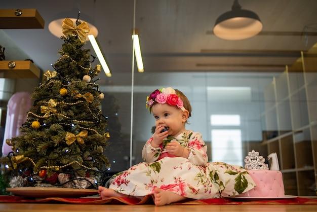 Piccolo bambino vicino all'albero di natale prima della festa di capodanno