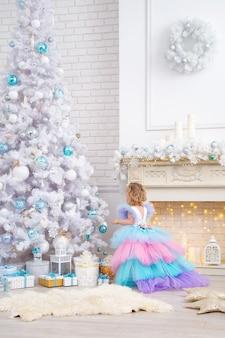 Il piccolo bambino si siede su un soffice tappeto e guarda l'albero di natale