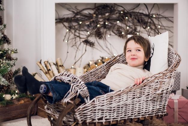 Il piccolo bambino si siede in una slitta sulle decorazioni di natale