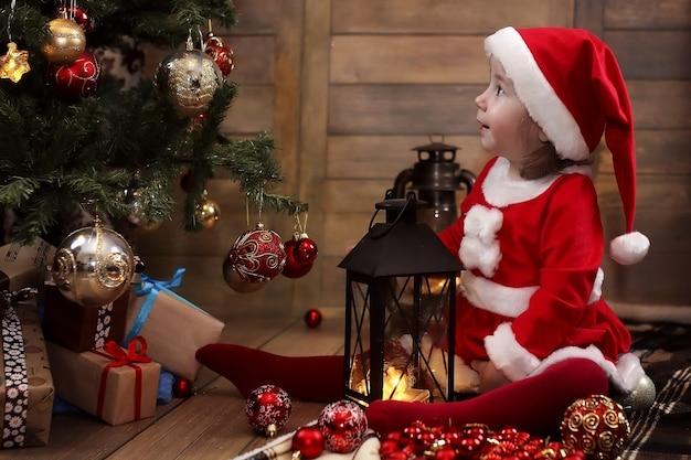 Piccolo bambino seduto per terra nella stanza davanti a un albero di natale decorato