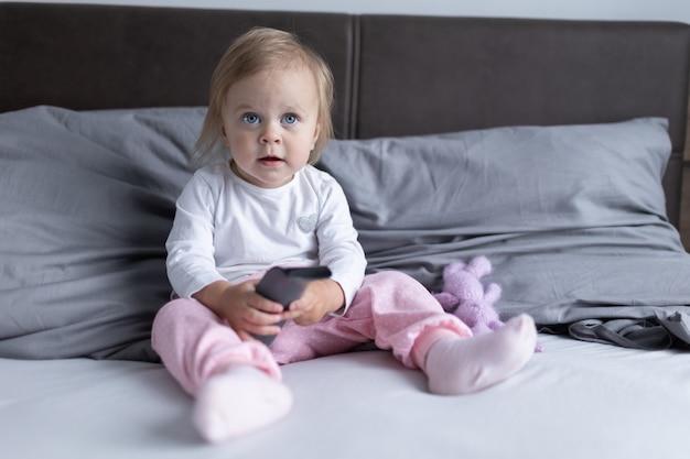 Il piccolo bambino con gli occhi azzurri si siede sul letto in camera da letto con un telecomando della tv