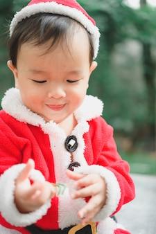 Piccolo bambino con vestito di babbo natale sul pavimento
