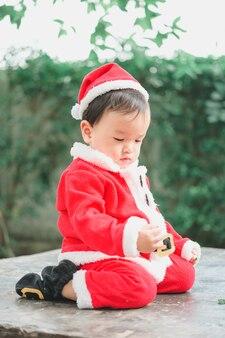 Piccolo bambino con il vestito di babbo natale guardando verso il basso