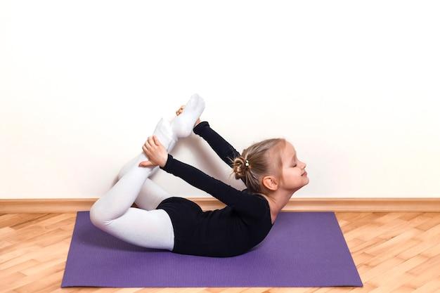 La piccola ballerina fa un allungamento sul tappeto