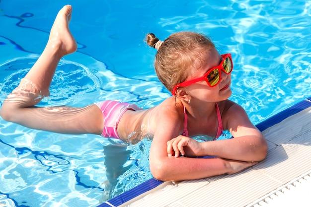Piccola ballerina in piscina d'estate