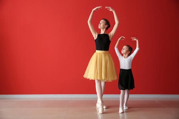 Piccola ballerina che si allena con l'allenatore in studio di danza