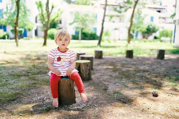 Il piccolo bambino a piedi nudi si siede su un ceppo di albero nel cortile