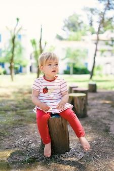 Il piccolo bambino a piedi nudi si siede su un ceppo di albero tree