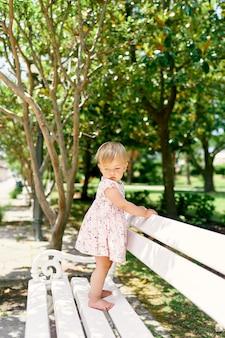 La piccola ragazza a piedi nudi in un vestito sta su una panchina nel parco