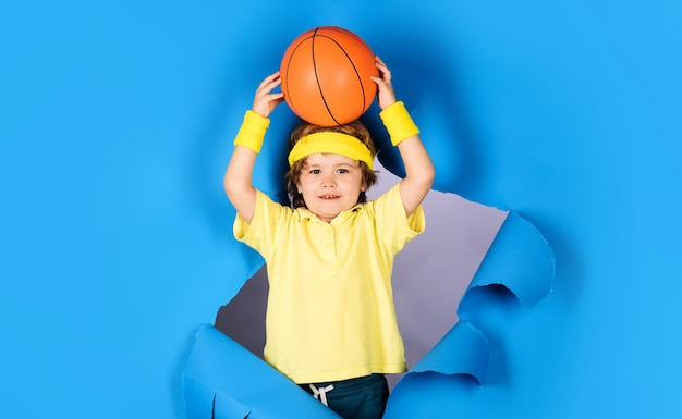 Piccolo giocatore di basket, bambino in abbigliamento sportivo lancia la palla, allenamento di basket, attrezzatura sportiva, attività sportive per bambini.