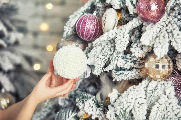 La piccola e bellissima bambina si veste con le mani dell'albero di natale che tengono la palla giocattolo da vicino