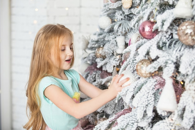 La piccola bella neonata veste l'albero di natale felice e alla moda nell'interno