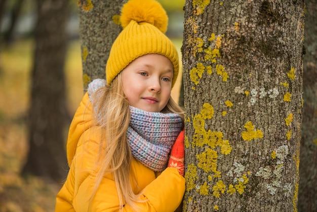 Piccola bella ragazza bionda in abiti gialli, autunno Foto Premium
