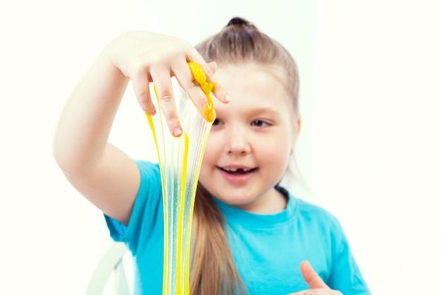Piccola bella ragazza caucasica che gioca con la melma gialla su una superficie bianca