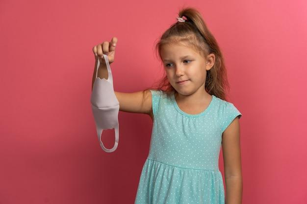 La piccola bellissima bambina in abito blu si toglie la maschera facciale e sorride su sfondo rosa