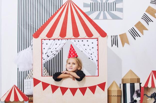 Piccola bellissima bambina nella stanza dei giochi per bambini che gioca nel circo festivo