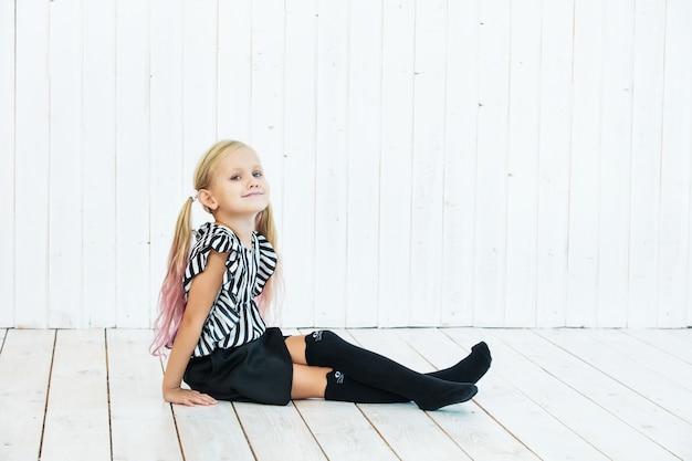 Piccola bella bambina elegante e alla moda su fondo di legno bianco