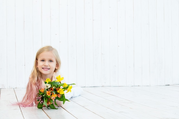Bambina bellissima bambina con bouquet di colori vivaci su fondo di legno bianco