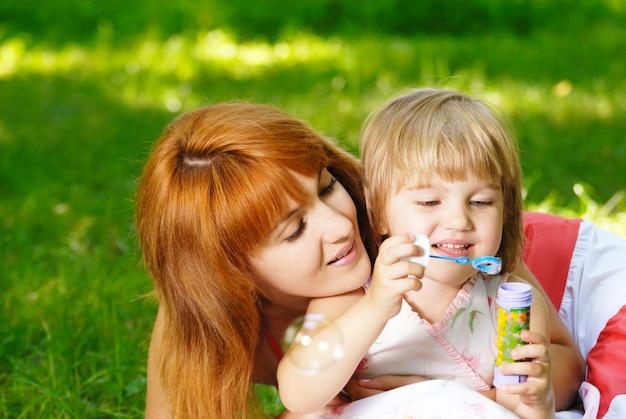 Bolle di sapone di salto della piccola bella ragazza con sua mamma
