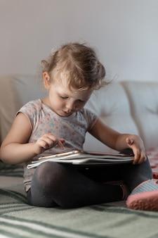 La piccola bella bambina si siede con un tablet sul divano e gioca. isolamento, casa, ragazzo