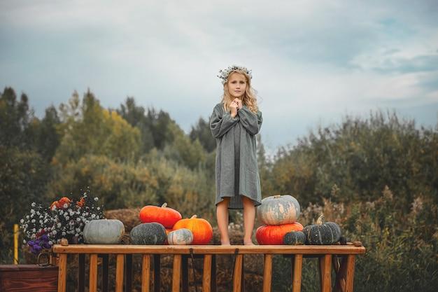 Piccola bella bambina con un carretto di legno con zucche colorate