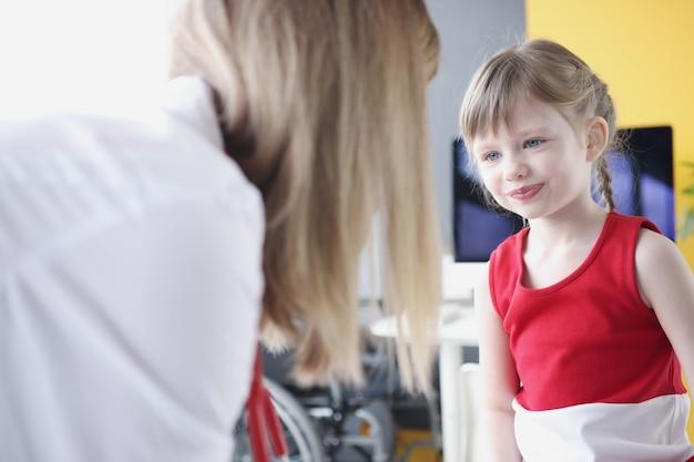 La piccola bella ragazza comunica con la dottoressa