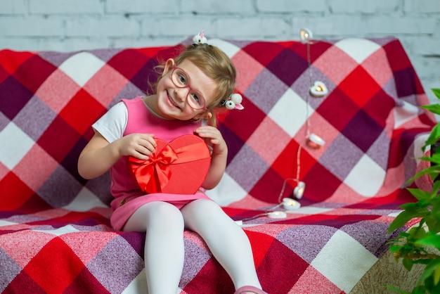 Piccola bella ragazza in bicchieri con cuore rosso scatola regalo e palloncino. vacanze di san valentino.