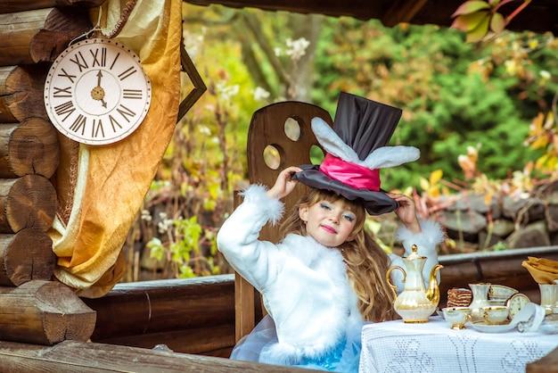 La piccola bella ragazza che tiene il cappello del cilindro con le orecchie gradisce un coniglio al tavolo