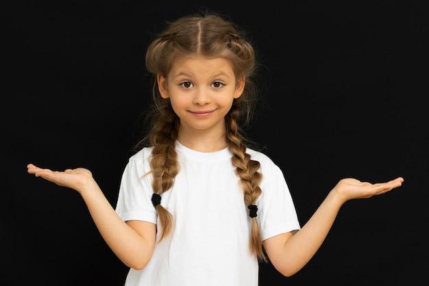 La piccola bella ragazza ama posare su uno sfondo nero.