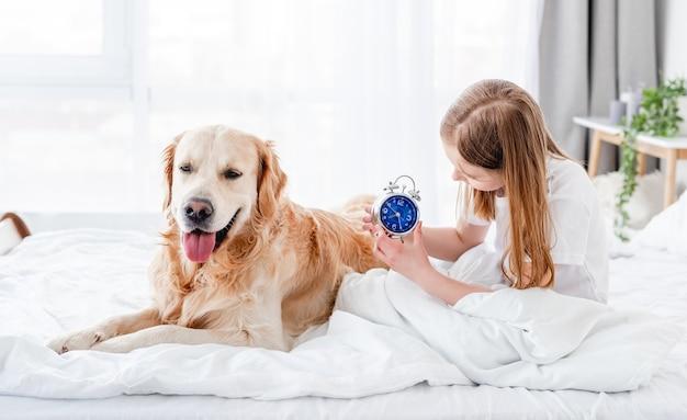 Piccola bella ragazza seduta nel letto al mattino e guardando l'orologio e il cane golden retriever sdraiato vicino a lei. ragazzo carino stare in camera da letto con cagnolino. bambino e labrador