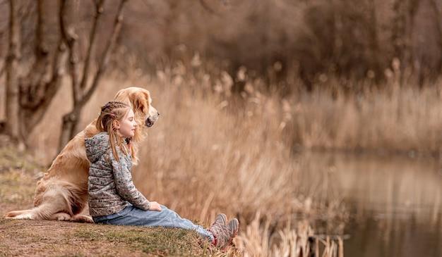 Piccola bella ragazza seduta con il cane golden retriever e guardando il fiume