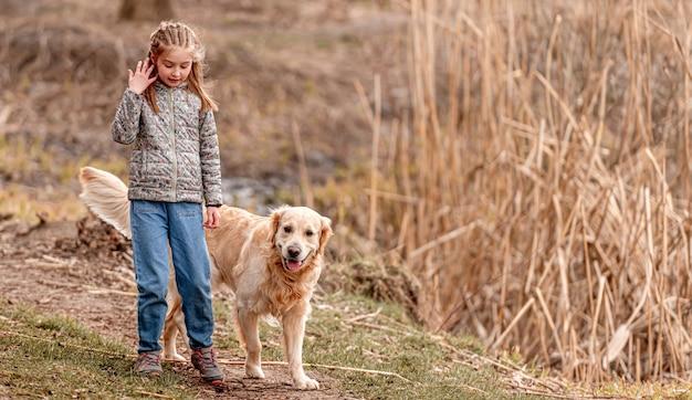 Piccola bella ragazza che cammina con il cane golden retriever sulla natura in primavera
