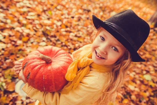 Piccola bella ragazza con i capelli biondi con grande zucca in autunno. halloween
