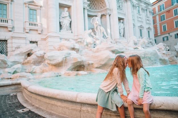 Piccole belle ragazze si avvicinano alla fontana fontana di trevi