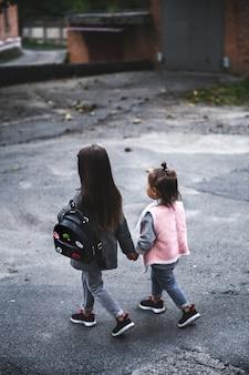 Piccole belle ragazze, vestite con stile, vanno per la mano sull'asfalto. relazioni, persone