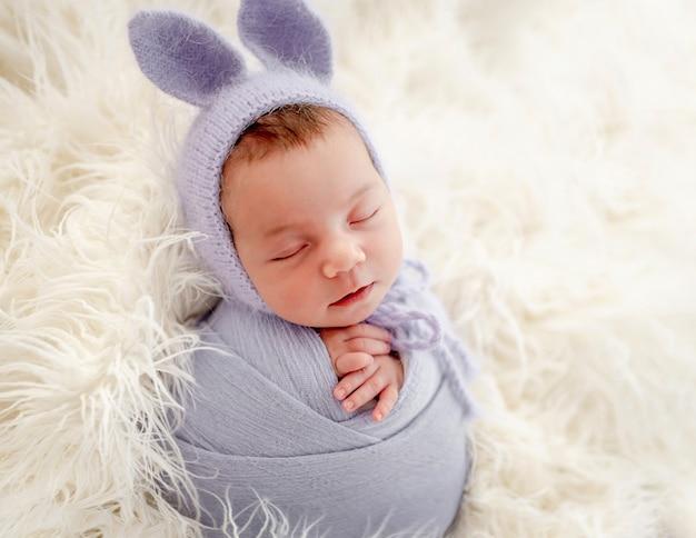 Piccola bella neonata fasciata in tessuto e indossa un cappello con orecchie da coniglio che dorme sulla pelliccia durante il servizio fotografico in studio. simpatico bambino neonato che fa un pisolino