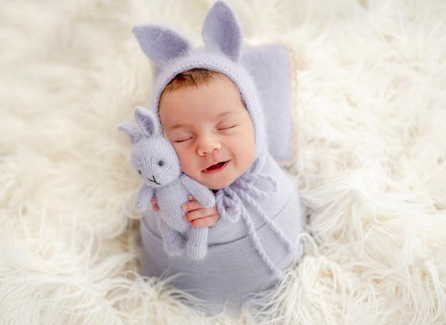 Piccola bella neonata fasciata in tessuto e indossa un cappello con orecchie da coniglio che dorme sulla pelliccia e sorride durante il servizio fotografico in studio. simpatico bambino neonato che fa un pisolino giocattolo in mani minuscole