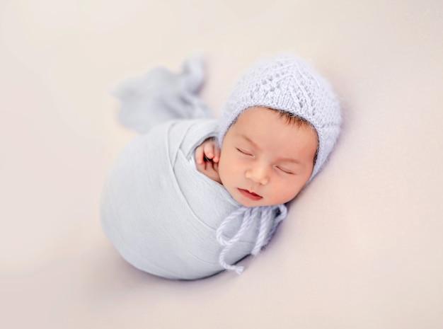 Piccola bella neonata fasciata in tessuto e con indosso un cappello lavorato a maglia che dorme durante il servizio fotografico in studio. simpatico bambino neonato che fa un pisolino a riposo