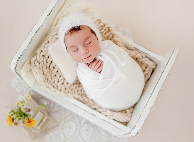 Piccola bellissima neonata fasciata in tessuto e con indosso un cappello lavorato a maglia che dorme in un piccolo letto progettato durante il servizio fotografico in studio. simpatico bambino neonato che fa un pisolino a riposo