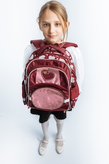 Piccola bella studentessa, con valigetta, muro bianco