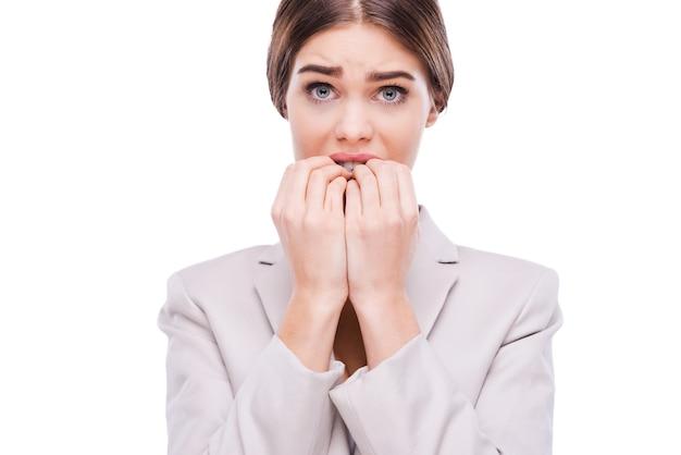 Un po' nervoso per questa faccenda. giovane donna d'affari nervosa che si mangia le unghie mentre sta in piedi su sfondo bianco white