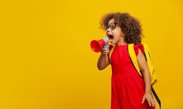 Piccola ragazza nera in abito rosso che tiene in mano e parla in un megafono grigio elettronico su giallo Foto Premium