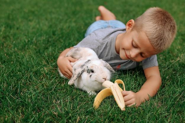 Un ragazzino biondo alimenta un coniglio dalle orecchie cadenti.
