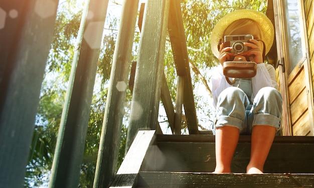 Bambina bionda godendo le vacanze estive presso la casa sull'albero. giardinaggio