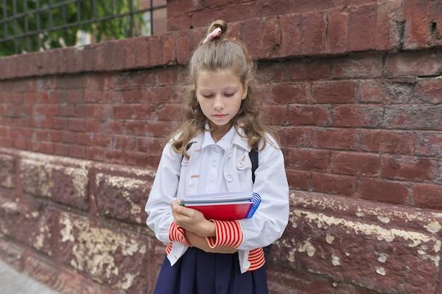 Piccola ragazza bionda con l'uniforme scolastica che tiene il taccuino